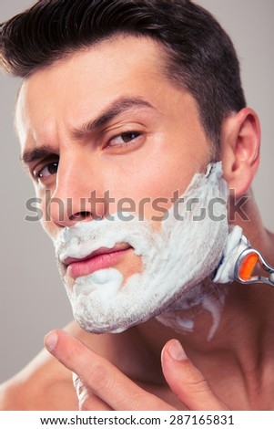 Handsome man shaving with foam and razor over gray background - stock photo