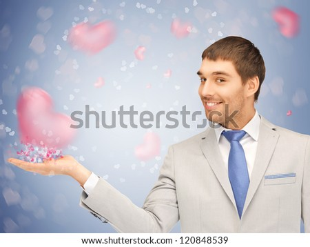 handsome man showing hearts on the palm of his hand - stock photo