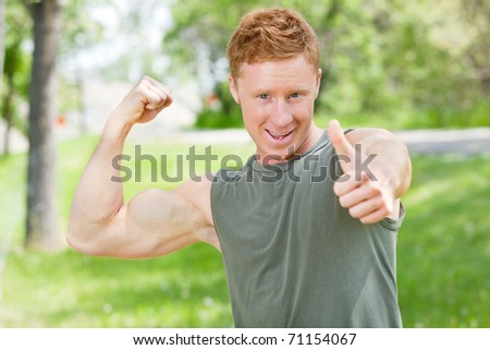 Handsome man showing thumbs up sign while flexing - stock photo