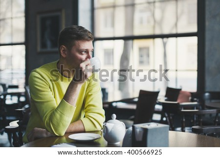 Handsome man sits at a table in an empty bar with a cup of tea in hand - stock photo