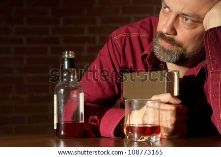 Handsome man sits quietly at his home at the table - stock photo