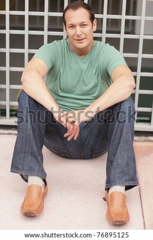 Handsome man sitting - stock photo