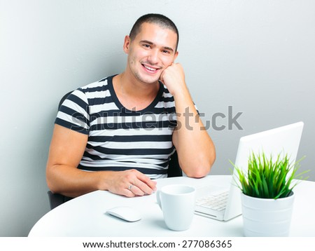 handsome man sitting at the table and using laptop computer - stock photo
