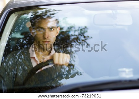 Handsome man sitting in a car - stock photo