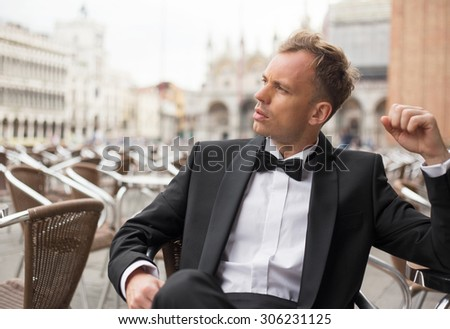 Handsome man sitting in cafe - stock photo
