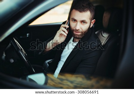 Handsome man sitting in car, talking on cellphone