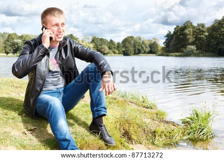 Handsome man sitting near river and calling on mobile phone
