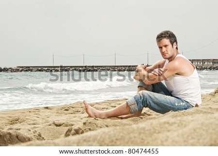 Handsome man sitting on a beach - stock photo