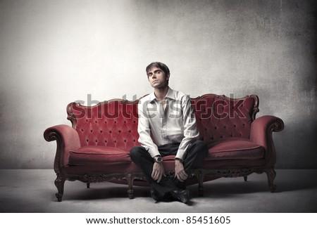 Handsome man sitting on a velvet sofa - stock photo