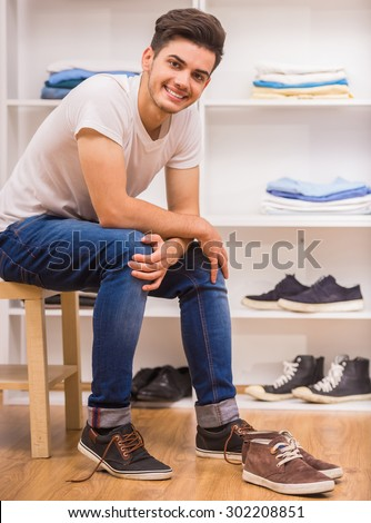 Handsome man sitting on chair at the dressing room and smiling at camera. - stock photo