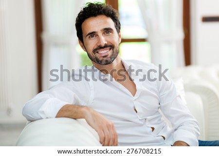 Handsome man sitting on his sofa - stock photo