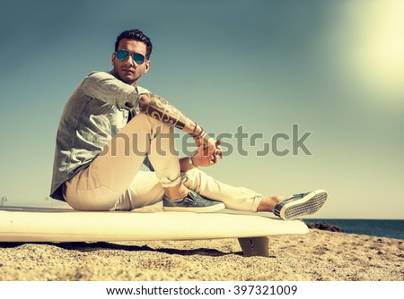 Handsome man sitting on surfboard at beach - stock photo