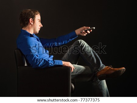 Handsome man sitting on the armchair in the dark changing TV channels with remote control - stock photo
