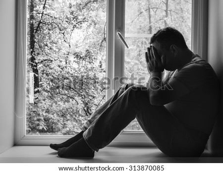 Handsome man sitting on the window-sill. Black and white photo - stock photo