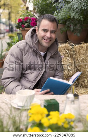 handsome man sitting outside in a cafe and reading a book - stock photo