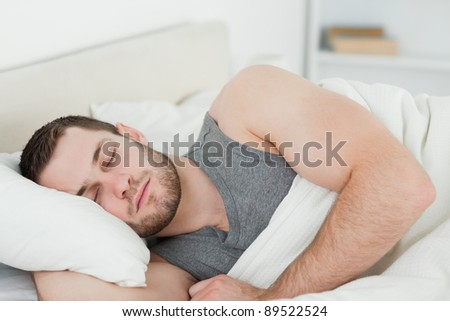 Handsome man sleeping in his bedroom - stock photo