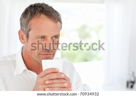 Handsome man smelling his coffee at home - stock photo