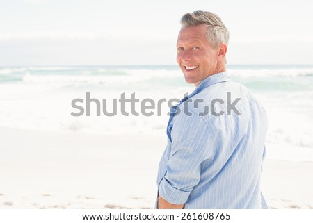 Handsome man smiling at camera at the beach - stock photo