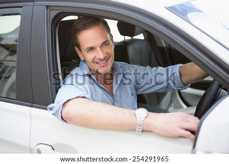 Handsome man smiling at camera in his car