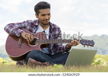 Handsome man smiling, playing guitar while looking at  laptop. Sitting on green grass. Nature background.