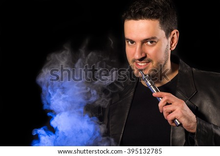 Handsome man smiling with e-cigarette custom mod and vapor - on the black background - stock photo