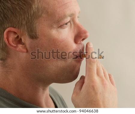 Handsome man smoking cigarette closeup - stock photo