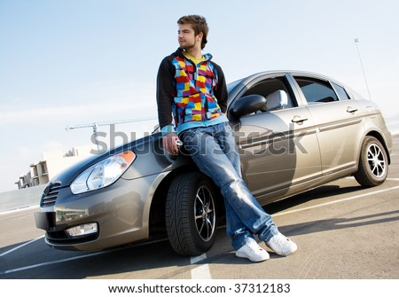 Handsome man standing near his new car - stock photo