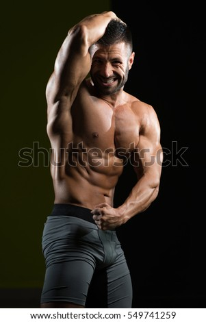 Handsome Man Standing Strong In The Gym And Flexing Muscles - Muscular Athletic Bodybuilder Fitness Model Posing After Exercises