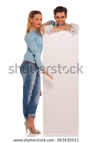 handsome man stands with hands crossed behind white blank sign while woman is presenting the board in isolated studio background - stock photo