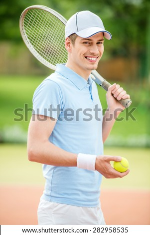 Handsome man stood in front of tennis court holding racket over shoulder. - stock photo