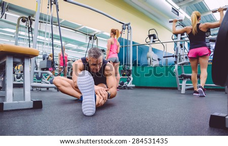 Handsome man stretching in a fitness center and two beautiful women doing exercises with dumbbells in the background - stock photo