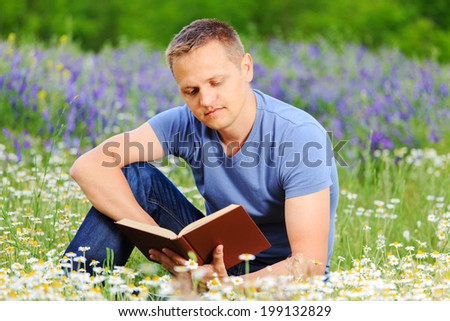 Handsome man studying outdoors with a book. - stock photo