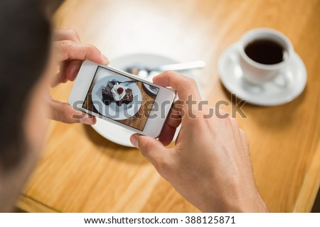 Handsome man taking a picture of his food in a pub - stock photo