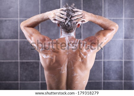 Handsome man taking a shower and enjoying it - stock photo