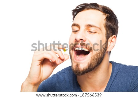 handsome man taking pills, isolated in white - stock photo