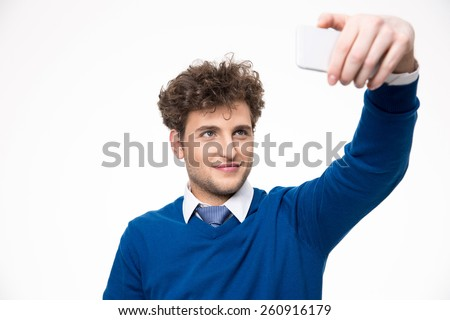 Handsome man taking selfie photo on smartphone over gray background - stock photo