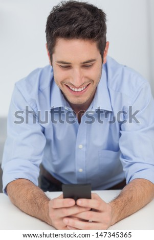 Handsome man text messaging with his smartphone - stock photo