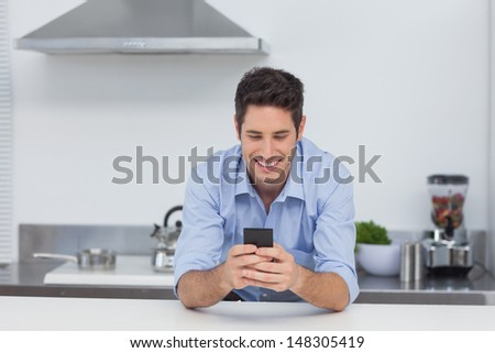 Handsome man texting with his smartphone in kitchen - stock photo