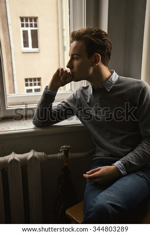 Handsome man thinking in home background