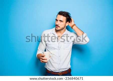 handsome man thinking on something and scratching his head, holding a cup of coffee in hands - stock photo