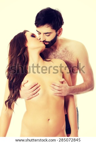 Handsome man touching woman's breast and kissing her.