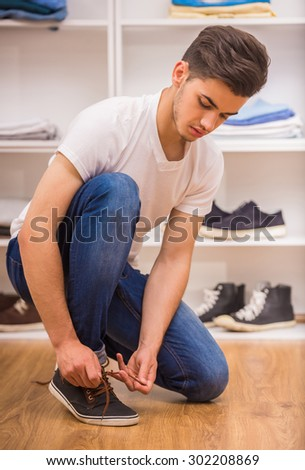 Handsome man tying shoe laces at the dressing room. - stock photo