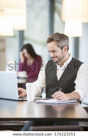 handsome man using a laptop in a cafe