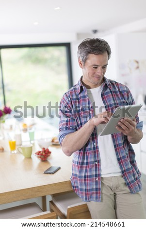 handsome man using digital tablet in the kitchen at the morning