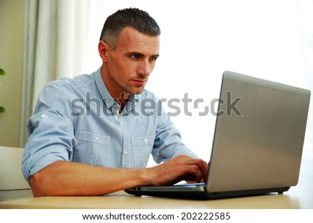 Handsome man using laptop - stock photo