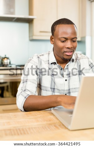 Handsome man using laptop in the kitchen - stock photo