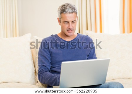 Handsome man using laptop on the sofa