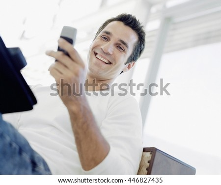 Handsome man using smartphone at home - stock photo