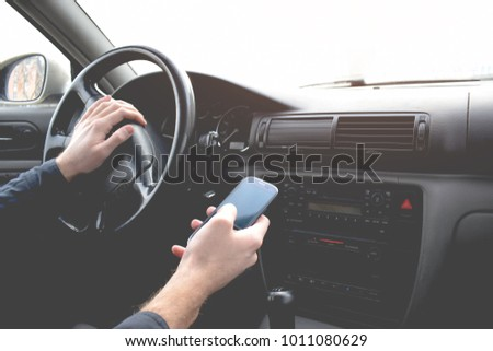 Handsome Man using smartphone while driving the car