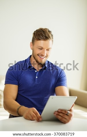 Handsome man using tablet pc at home